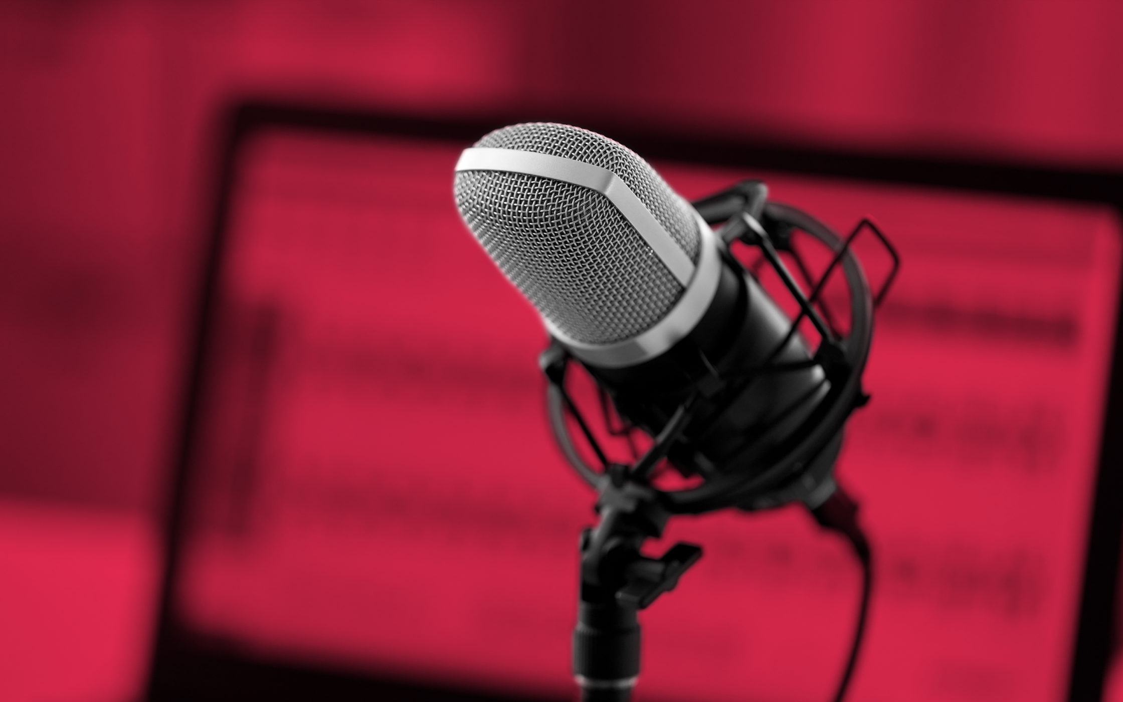 A podcast microphone set against a maroon background